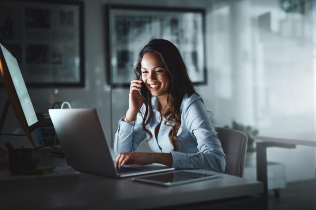 En dam som pratar i telefon medan du använder den bärbara datorn | KFX